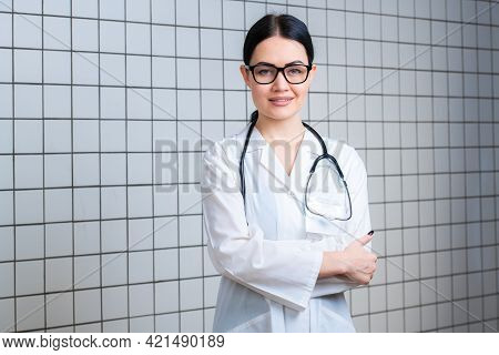 Young Beautiful Female Doctor In White Surgical Coat With Black Stethoscope And Blue Paper Holder In