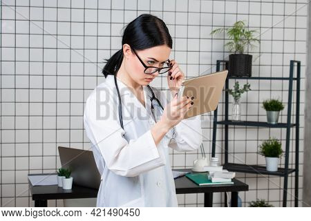 Portrait Of Female Doctor Using Her Digital Tablet In The Office.