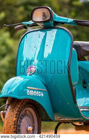 Galle, Sri Lanka - 06 21 2020: Vespa Scooter Front Close Up View, Parked In A Muddy Road On A Rainy