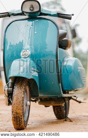 Vespa Scooter Front Close Up View, Parked In A Muddy Road In A Rainy Day. Sky Blue Vintage Classic M