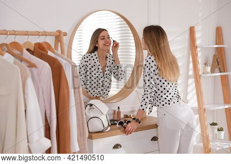 Young Woman Doing Makeup Near Mirror At Home. Morning Routine