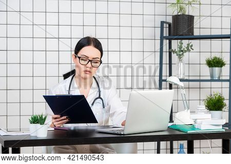 Woman Lab Assistant Working At Her Desk, Hospital, Documents
