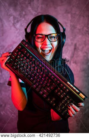 Nerd Geek Young Adult Women Holding Gaming Keyboard Over Colorful Pink And Blue Neon Lit Wall. Gamin