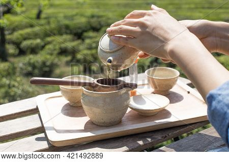 Hand Pouring Green Tea With Green Tea Field As A Background.