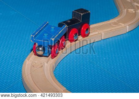 Wooden Toy Train With A Wagon On A Wooden Railway In The Children's Playroom As A Toy For Boys And G