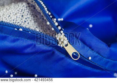 Electrified Lightweight Foam Filler Stuck To The Zipper, Hands, Blue Fabric.