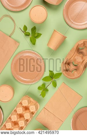 Flat Lay Composition With Eco-friendly Tableware And Kraft Paper Food Packaging On Green Background.