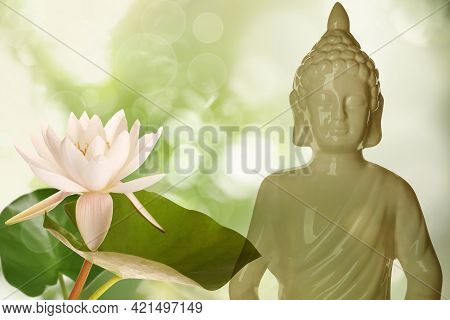 Beautiful Ceramic Buddha Sculpture And Lotus Flower On Color Background
