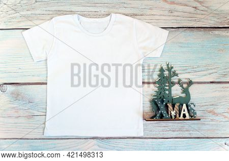 Christmas Kid Shirt Mockup - White Tshirt On Wooden Background. Stock Photo.