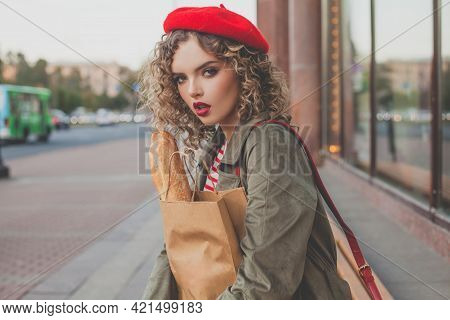 Stylish Woman In Red French Beret Holding Fresh French Baguette Outdoor