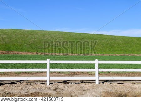 Low Grassland Hillside Hills Pasture With Bright Sunny Blue Sky And Wooden White Picket Farm Livesto