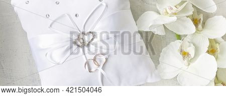 Banner With White Pillow For Wedding Rings With Rings And Rhinestone Hearts Near White Orchid On A W