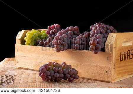 Grapes, Wooden Box With Grapes In Brazil, Written Grapes In Portuguese Next To The Box, Black Backgr