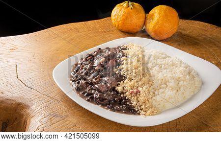 Brazilian Feijoada, White Dish With A Delicious Brazilian Feijoada, Rice And Farofa, With Two Orange