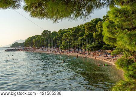 Makarska, Croatia - September 5, 2019: Beautiful beach at Adriatic Sea in Makarska Riviera, Dalmatia, Croatia. Unidentified people enjoy beach holidays in Croatia