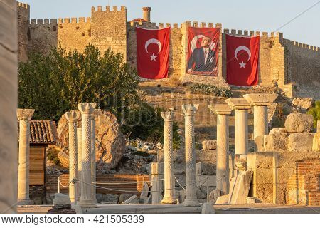 Selcuk, Turkey - November 4, 2020: Ruins of the Johns Basilica with an ancient Ayasuluk Castle at background in Selcuk town, Turkey. Turkish national flag and Portrait of Ataturk