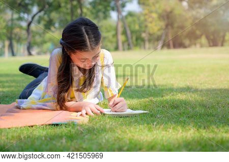 A Half-thai-european Girl Lay To Rest And Write In A Notebook While Learning Outside Of School In A