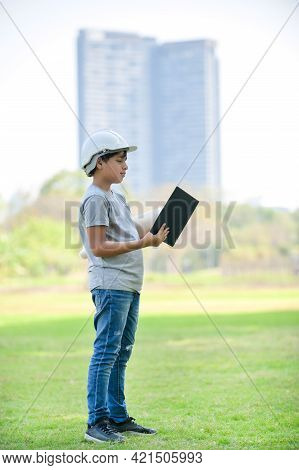 A Half-thai-indian Boy Wearing A Helmet Holds A Blueprint And Expecting That In The Future Will Be A