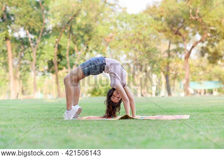 Half Thai-european Girls Exercising In Gymnastics As Part Of Their Learning Outside Of School In The