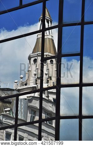 Reflection Of An Old House With A Tower In The Window Panes Of A Modern Building. Old House Against