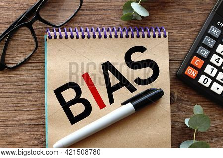 Bias. Lies On A Wooden Background, A Notebook With Craft Pages. Text On Notepad.