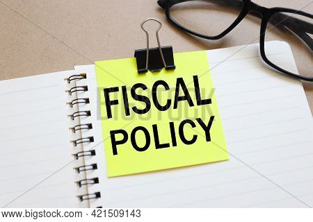 Fiscal Policy. Text On White Notepad Paper Near Calendar On Wood Craft Background