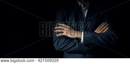Businessman In Suit With Crossed Arms Standing On Dark Black Background. Copy Space