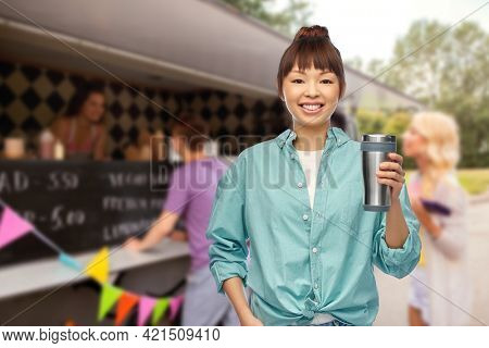 sustainability and people concept - portrait of young asian woman in turquoise shirt with thermo cup or tumbler for hot drinks over food truck background