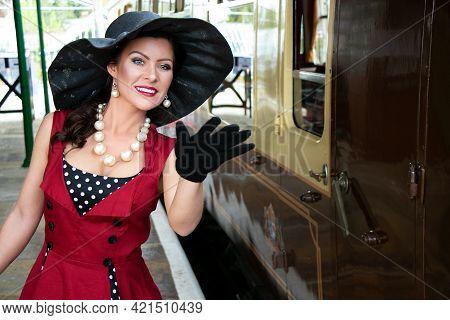 Beautiful Woman In Vintage Red Polka Dot Dress Standing On Vintage Railway Platform.