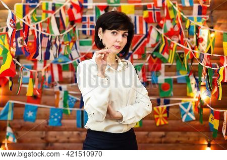 A Strict Woman In A White Blouse Holds Glasses Against The Background Of Flags.