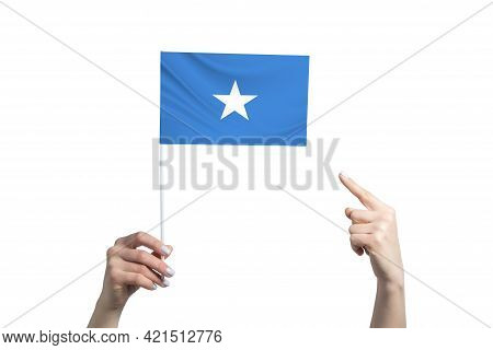 A Beautiful Female Hand Holds A Somalia Flag To Which She Shows The Finger Of Her Other Hand, Isolat