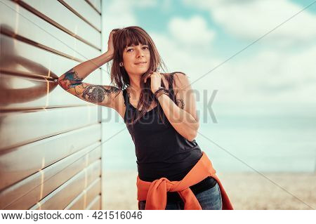Young Beautiful Smiling Woman With Tattoos Poses, Leaning Against A Wooden Wall. In The Background,
