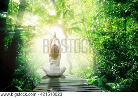 Conceptual Rear View Portrait Of Young Woman Sitting In Yoga Position On Path With Hands In Air. Gir