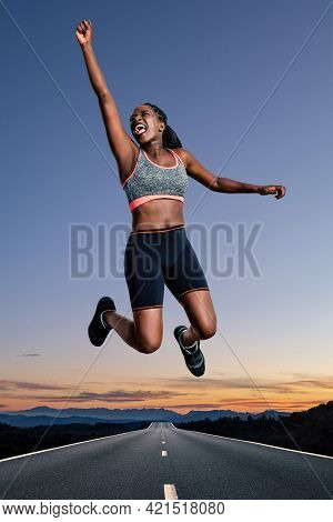 Full Length Portrait Of Young African American Female Athlete Jumping Outdoors.girl Shouting With Ar