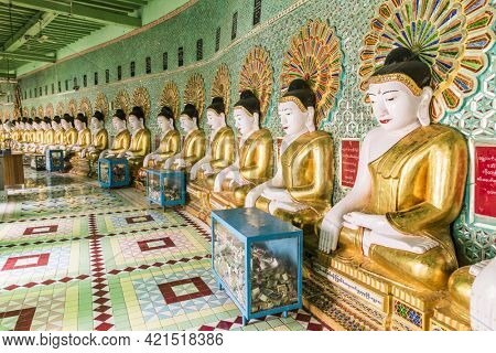 SAGAING, MYANMAR - JANUARY 30, 2016: Row of golden Buddha statues and offering boxes inside U Min Thonze Sel Pagoda located on Sagaing Hill. Mandalay Region, Myanmar