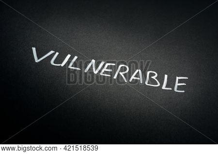 Handwritten Word Vulnerable On The Dark Paper.