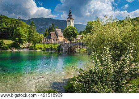 Flowery Lake Shore And Old Stone Bridge Over The Lake Bohinj. Traditional Old Church On The Shore Of