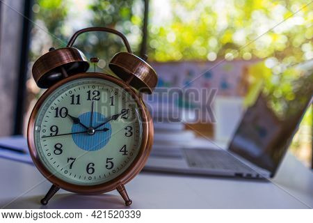 Retro Alarm Clock Vintage And Background Laptop Computer. The Concept For Time Management And Countd