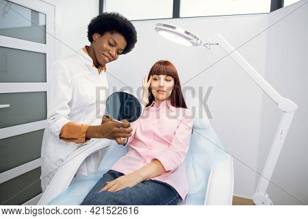 Female African Doctor Cosmetologist Is Consulting Woman Client Who Looking At Mirror In Beauty Clini