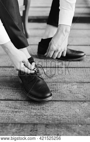 Black And White Photography. A Young Man Puts On Black Shoes And Ties The Laces, Close-up Of Male Ha