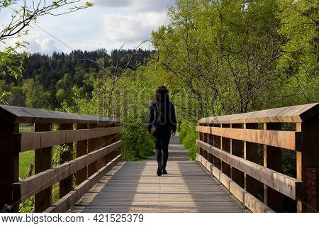 Woman Walking On A Wooden Path With Green Trees In Shoreline Trail, Port Moody, Greater Vancouver, B