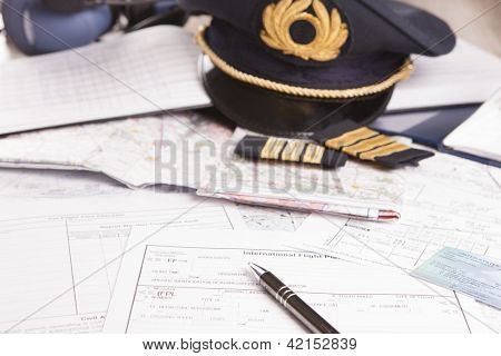 Close up of an airplane pilot equipment including hat, epaulettes and flightplannig papers