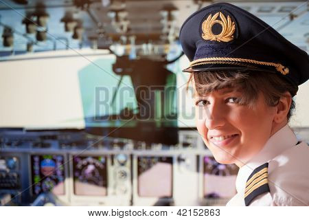 Beautiful woman pilot wearing uniform with epaulets, hat with golden wings sitting inside airliner with visible cockpit during flight. poster