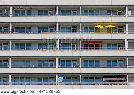 Facade Of A Big Apartment Building With Yellow Sunshades On One Of The Balconies