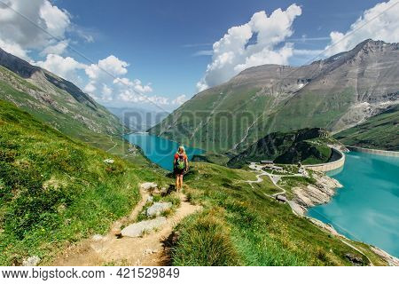 Beautiful Scenic View Of High Mountain Lakes.girl Hiking To The Mooserboden Dam In Austrian Alps.act