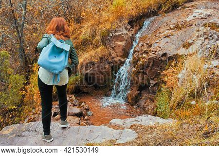 Red-haired Female Tourist With A Backpack. A Woman Admires A Small Waterfall In The Forest. Autumn L