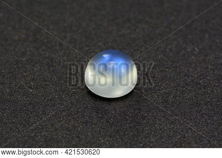 Natural Adularia Blue Sheen Round Cabochon Moonstone. Loose Gem On Gray Textured Leather Background.