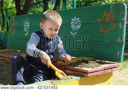 Omsk, Russia - June 21, 2019. A Charming Little Boy In A Tracksuit Plays On The Playground With Toys
