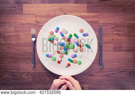 Overuse Of Drugs, Dietary Supplements And Vitamins Concept. Person Prepared For Eating With Cutlery