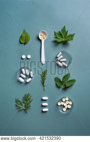 Homeopathy, Naturopathy And Alternative Herbal Medicine Concept. Capsules And Pills, Green Plant Lea